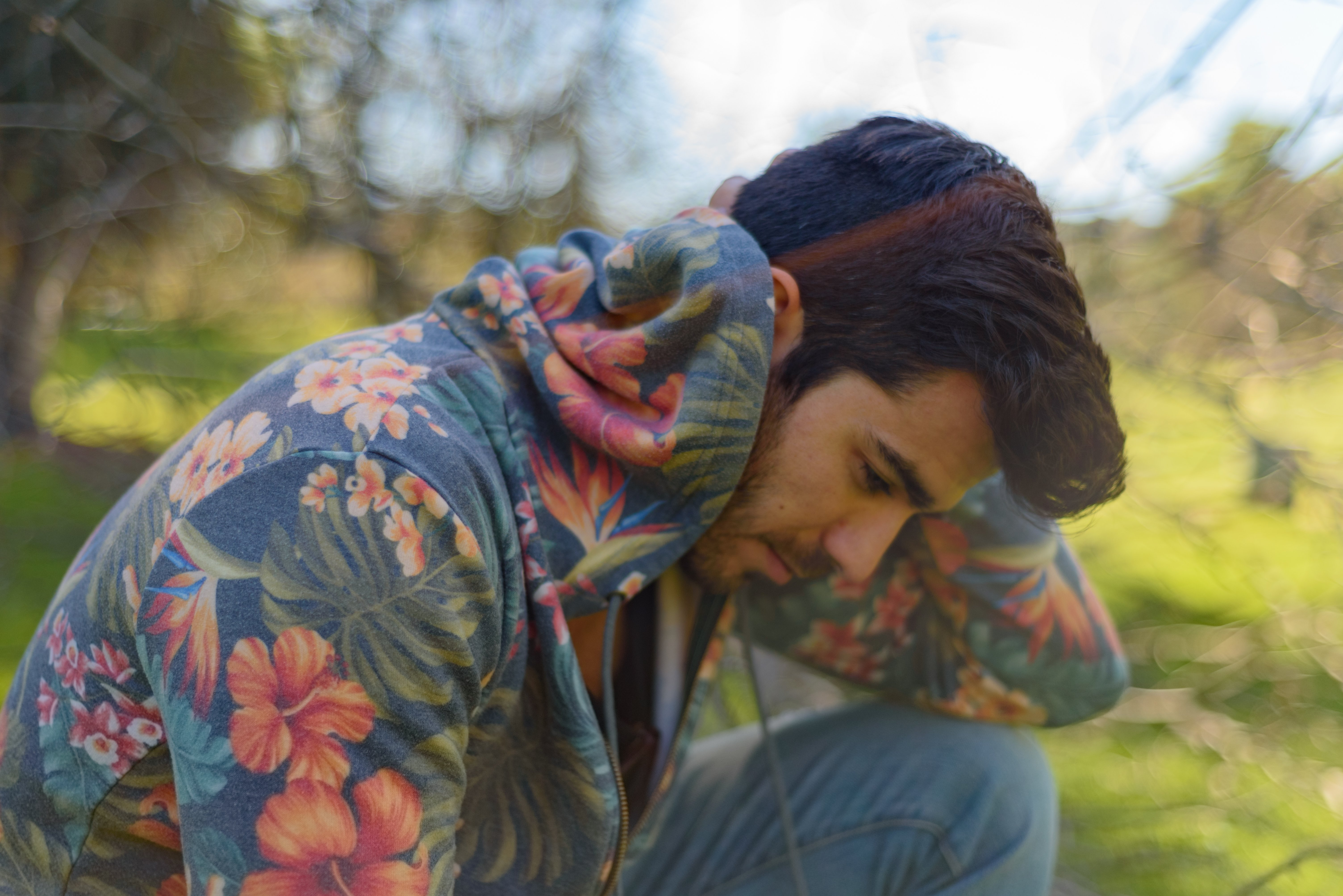 Model posing in a park in Los Angeles, California with a floral print hoodie.