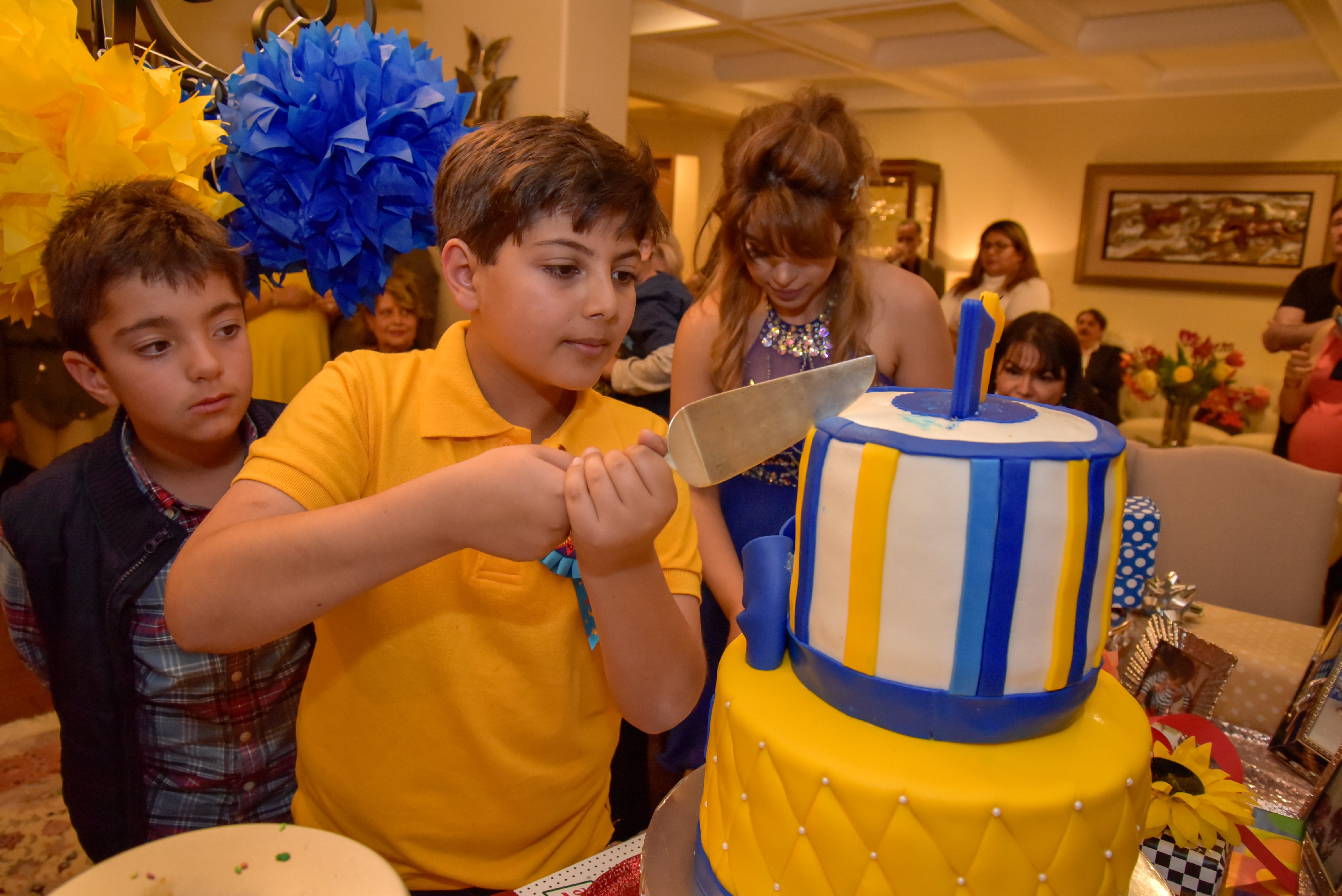 Photo of a child cutting his eleventh birthday cake for a family birthday party I was hired to shoot.