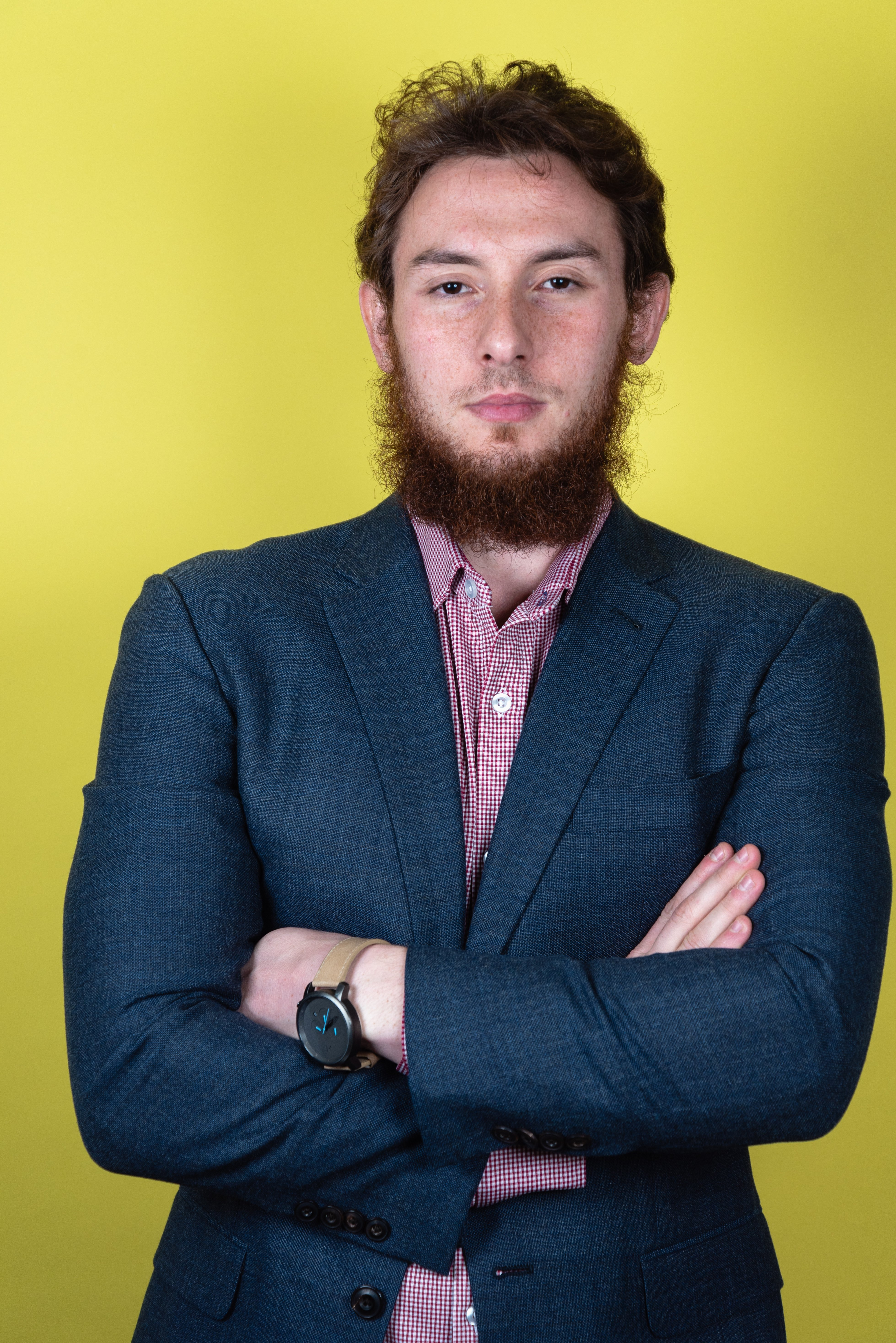 Business headshot of a client in a suit contrasted by a complementary tone of a yellow background.