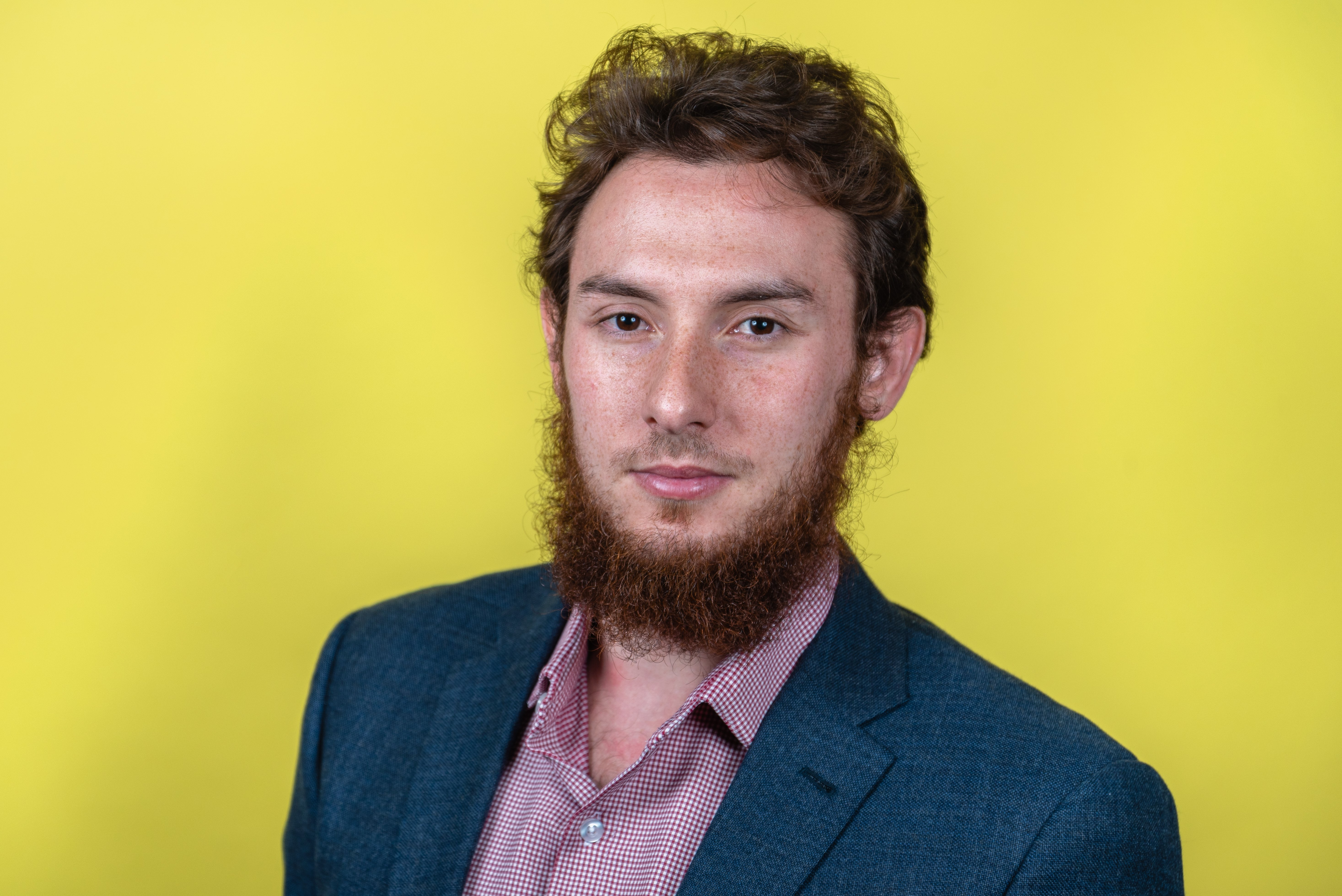 Head-shot taken for a client in a blue-gray suit contrasting in front of a yellow background for company branding,