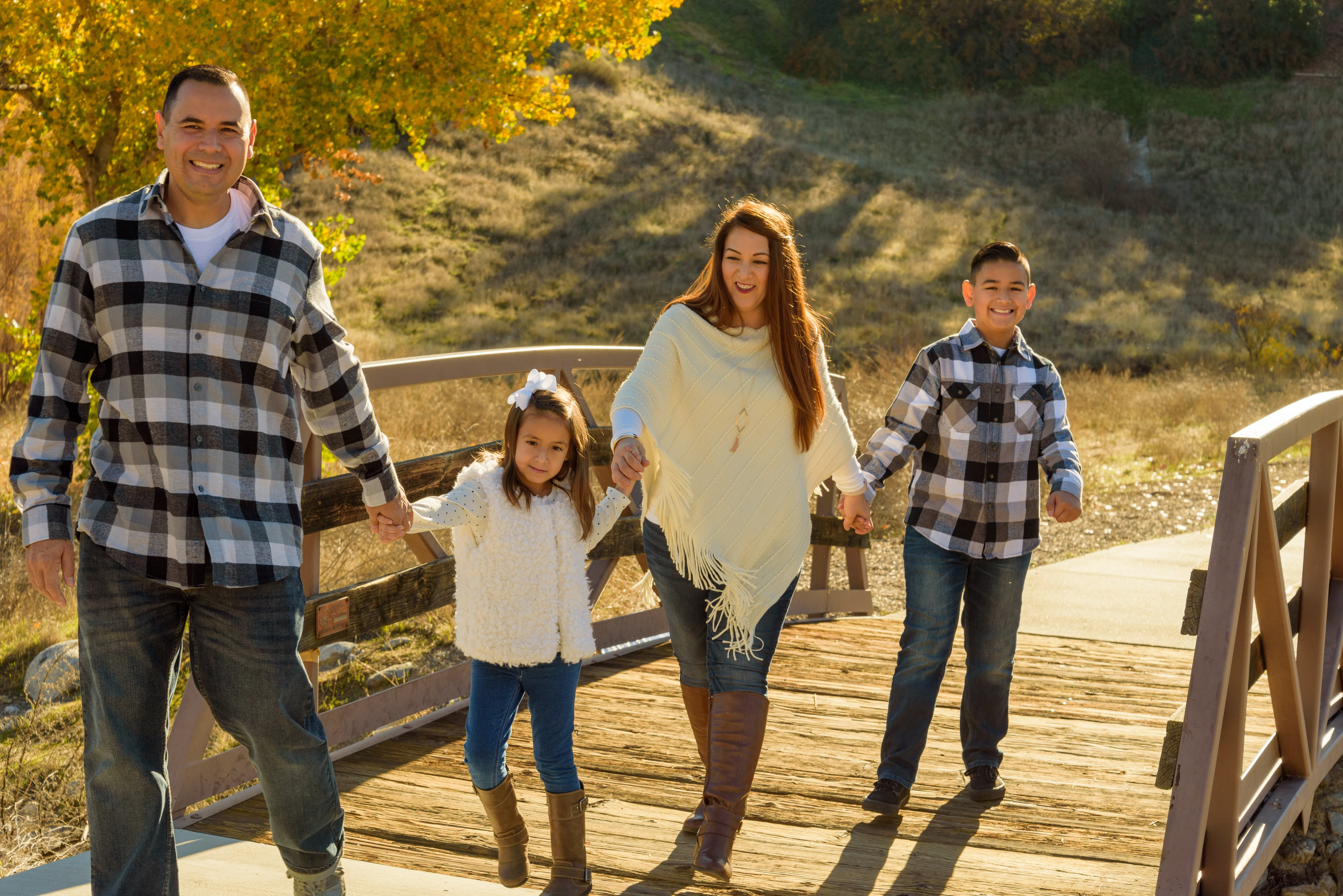 Family portrait taken in Santa Clarita with a family of four including two young children holding hands crossing over a bridge and smiling.