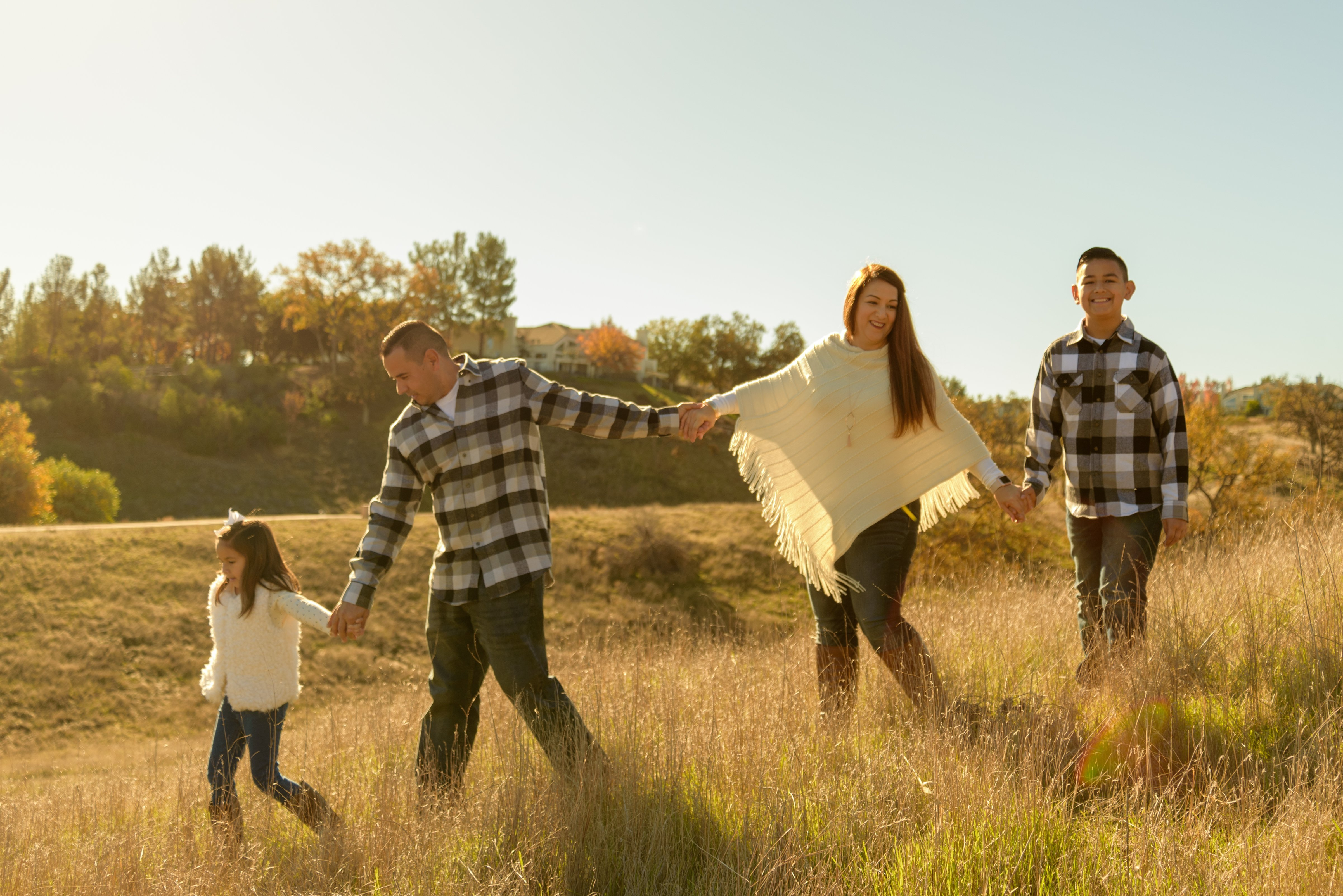 Family fall portraits with the sunrise giving a beautiful back-lit effect on the colors and exposure of the image.