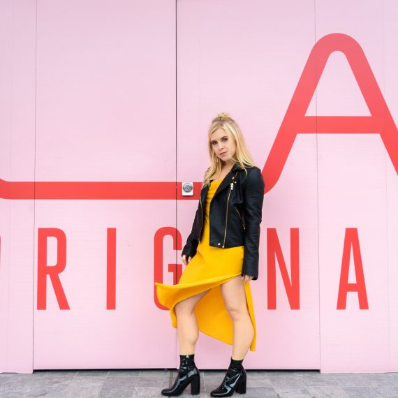 "Model standing in front of a sign ""LA Original"" that is shaded in pink contrasting with her black jacket and yellow dress."