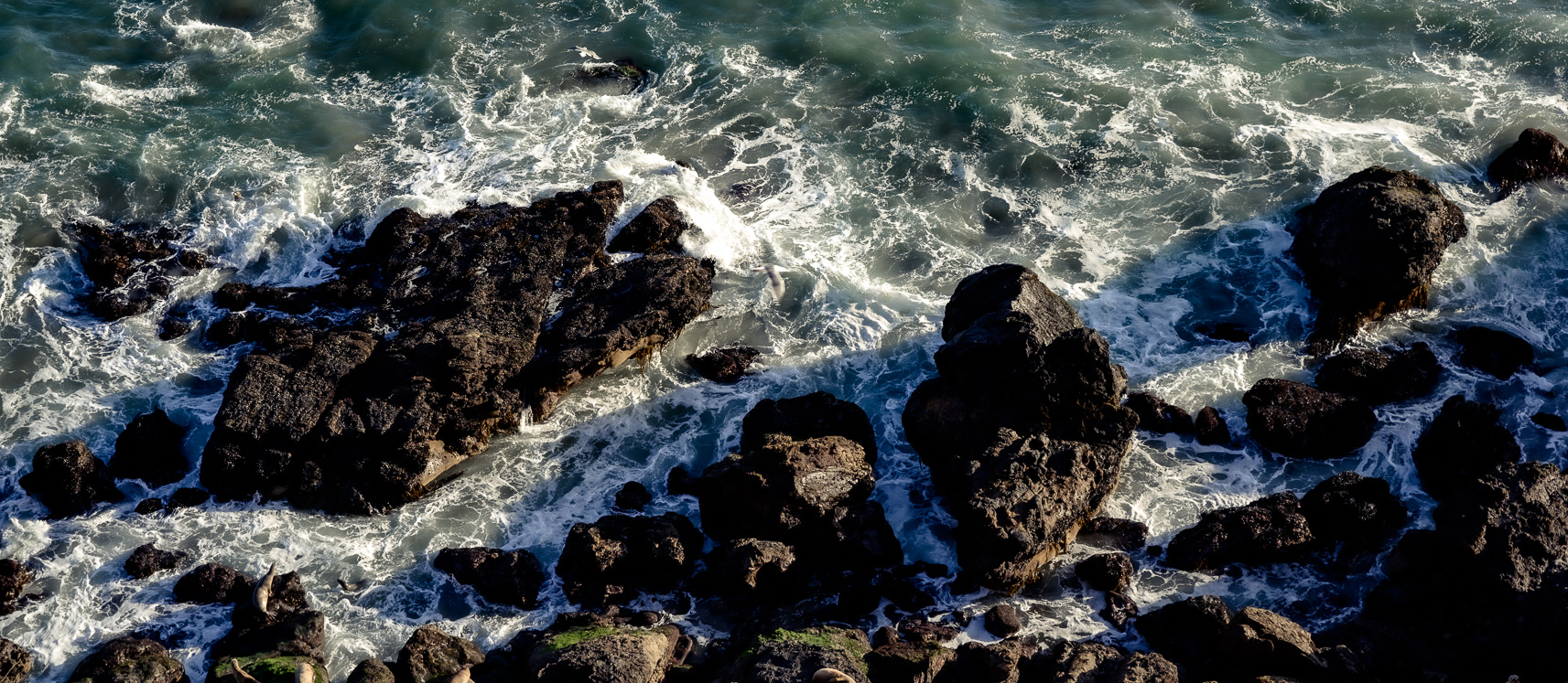 Top down view of an aerial photo looking at the waves crashing into the rocks on the coast of California.