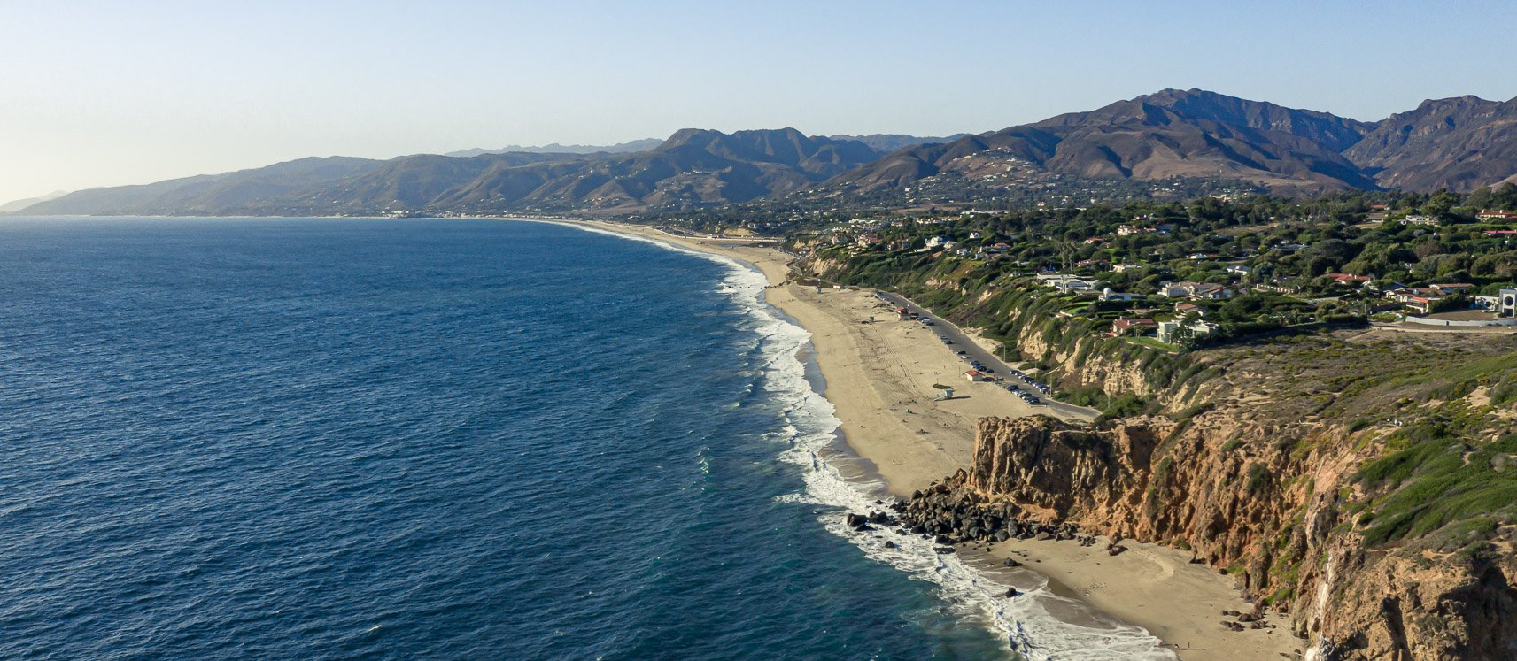 Panoramic aerial photo of California Coast in Malibu with the beach, ocean, rocks, and suburbs in view.