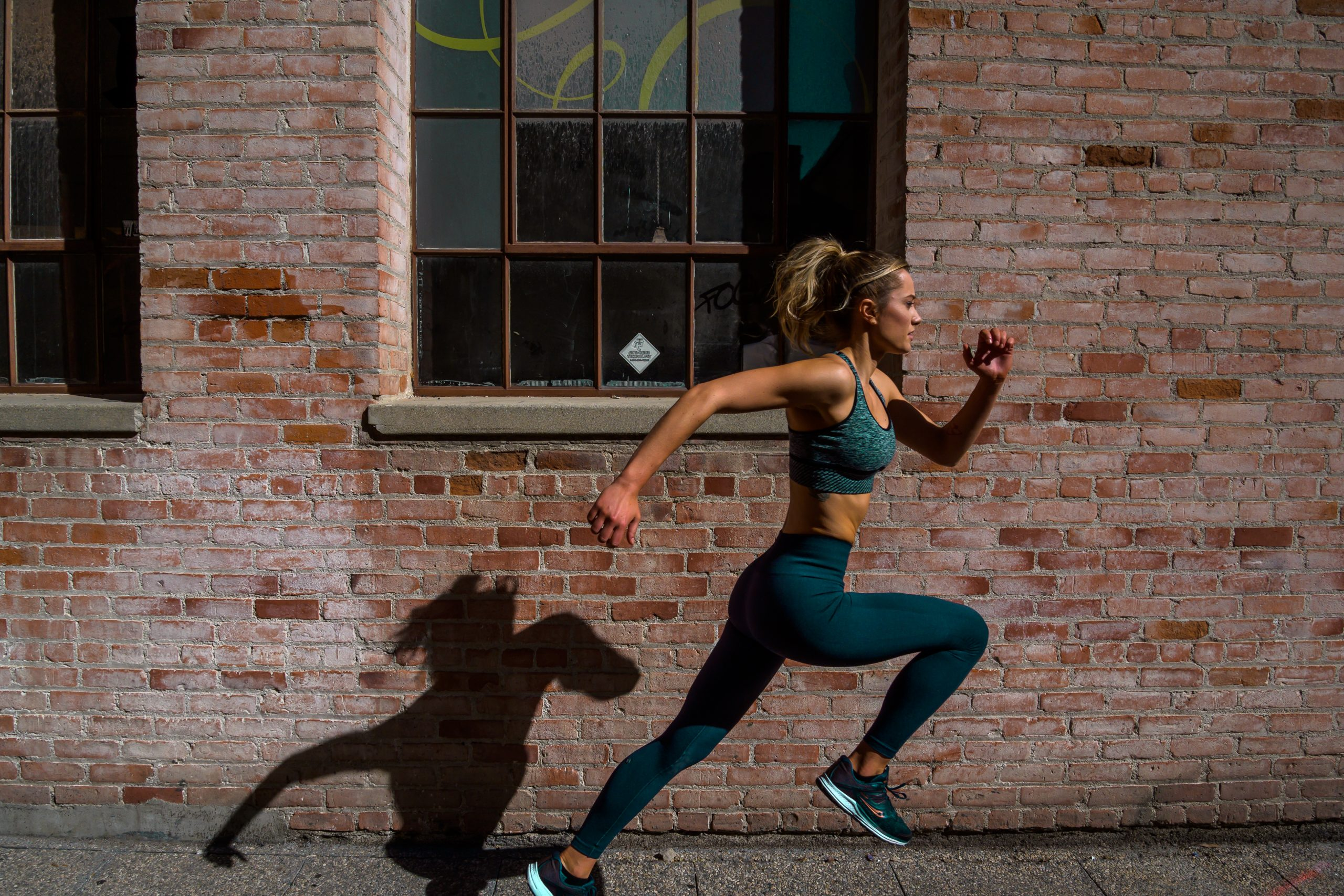 Carly Lane running for a sports commercial shoot show casing athleticism and casting a cool shadow on the brick wall behind her.